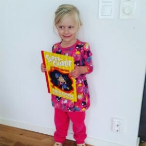 Super-nöjd tjej med sin Super-Charlie bok