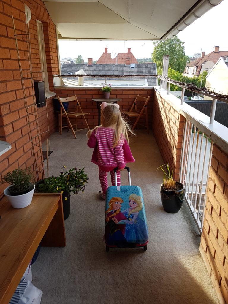 Här är hon lycklig över att få åka till farmor mes sin gena resväska