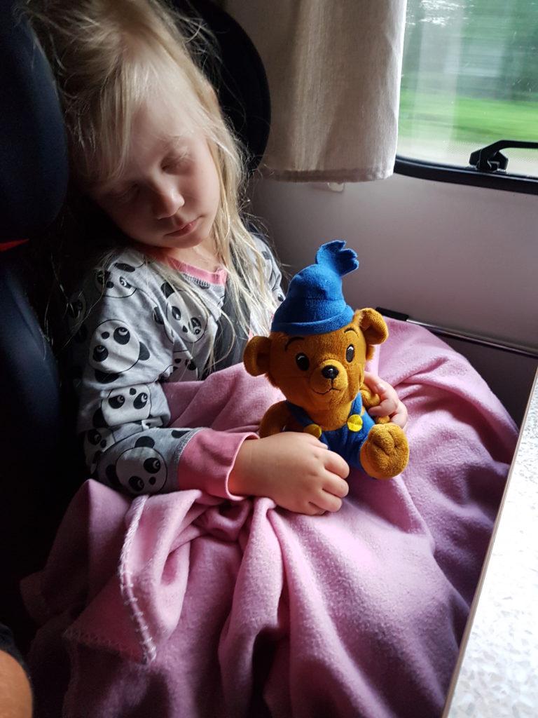 Liten trött tjej somnar med sin Bamse